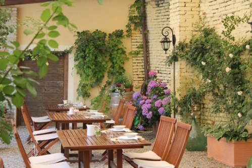 Tables set for breakfast in the loggia at La Villa Hotel,